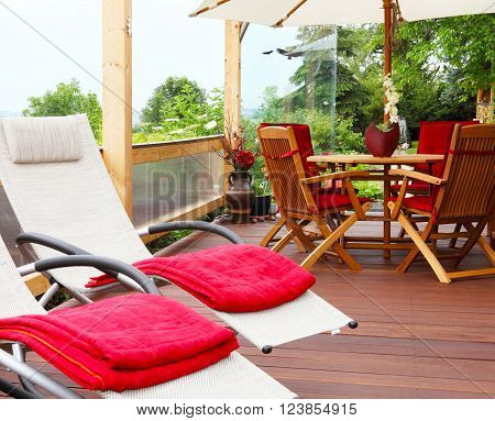 Two deck chairs with red rugs are on a terrace