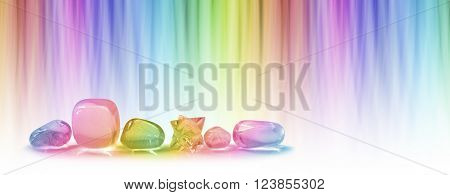 Healing crystals and color healing website header -  A  row of five tumbled healing crystals and a merkabah against a linear graduated chakra rainbow color background with plenty of copy space