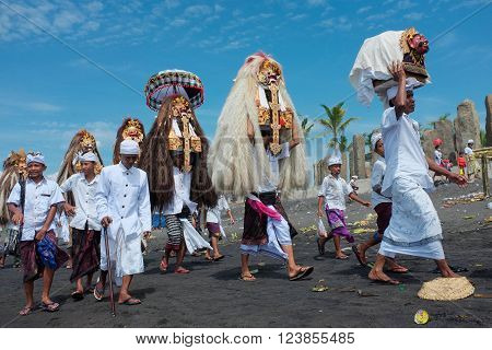 BALI INDONESIA - March 6 2016: Balinese Hindu devotees carry masks and sacred temple effigies along the beach during a Melasti ceremony on March 6 2016 at Purnama Beach in Bali Indonesia.