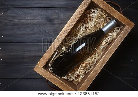 Bottle of white wine in a wooden crate with wood shavings on a dark wooden surface