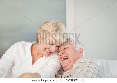 Happy senior couple laughing in bed at home
