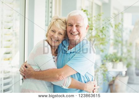 Portrait of happy senior couple hugging at home