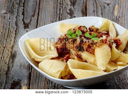 Delicious Conchiglie Giganti Pasta (Giant Pasta Shells) with Meat Sauce Bolognese in White Bowl closeup on Rustic Wooden background
