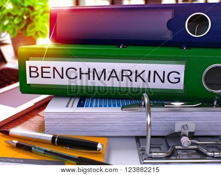 Green Office Folder with Inscription Benchmarking on Office Desktop with Office Supplies and Modern Laptop. Benchmarking Business Concept on Blurred Background. Benchmarking - Toned Image. 3D.