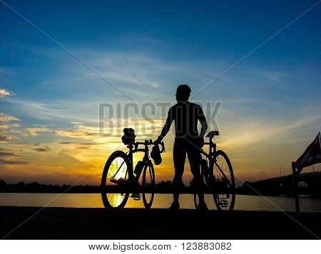 Bicycle rider stand on the river watching the sunlight and  relax