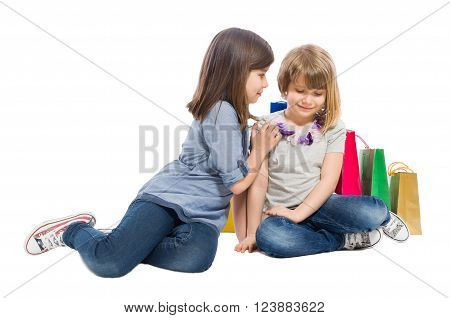 Young shopping sisters playing on white background
