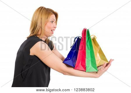 Surprised or excited woman holding heavy shopping bags on her arms isolated on white background