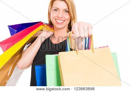 Confident shopping woman holding shopping bags to the camera