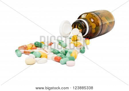 Bottle and various spilled pills on white table