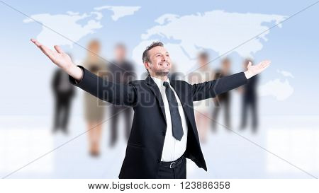 Successful business man with arms outstretched or outspread with business people background
