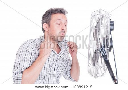 Sweaty man opening shirt in front of cooling fan as refreshing in hot summer concept