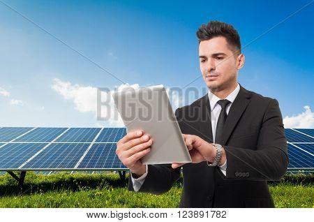 Modern businessman holding wireless tablet on solar power panels background