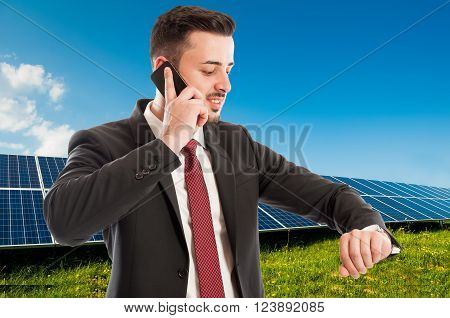 Busy businessman or salesman using phone and checking time on photovoltaic field background