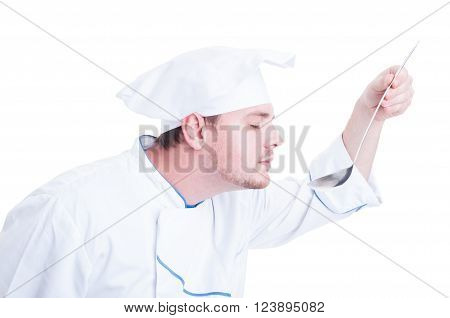 Chef or cook smelling flavor soup from ladle isolated on white