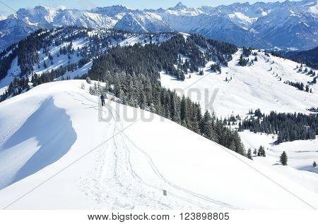 Wandelaar in de sneeuw op de kam van de berg