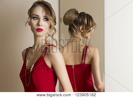 elegant woman with hair-style and make-up looking herself in the mirror and wearing fashion red dress