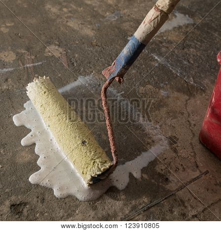 Priming Concrete floor before laying tiles on it, the final preparatory stage for strengthening the surface