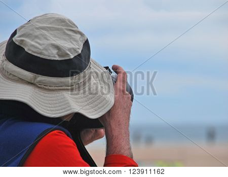 Paparazzi taking a picture. Unrecognizable photographer with a hat about to take pictures hidden under a big hat.