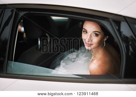 Close-up portrait of elegant bride in a car window. (beautiful bride with freckles)