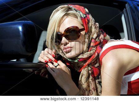 modern fashion blonde woman in dark sunglasses in the city