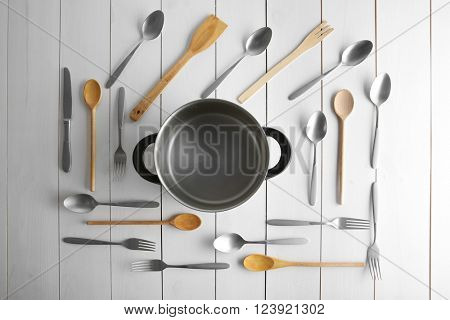 Saucepan and flatware on white table, top view