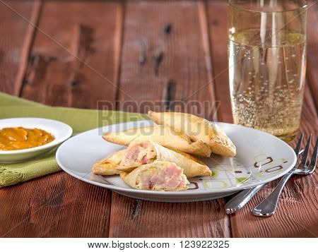 Ham and cheese empanadas, empanadas mixtas, a typical Peruvian dish served on white plate on wooden table top.