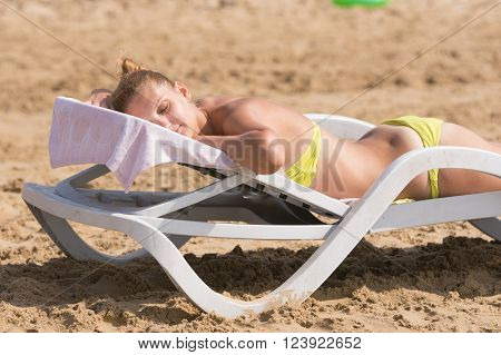 Young Girl Lying On A Deck Chair Back Up, Turning His Head And Eyes Closed