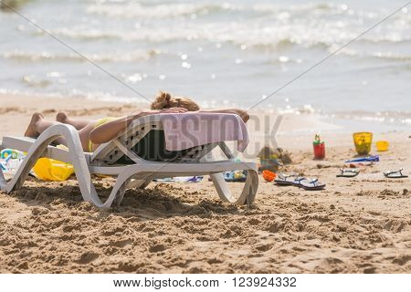 On The Sea Beach Near The Water With A Beach Chair Sunbathing Girl, Spanking And Childrens Sand Toys