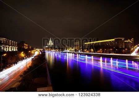 Moscow, Russia - September 17, 2014: Moscow Kotelnicheskaya Embankment Building and ships on Moskva river at night - Time-lapse