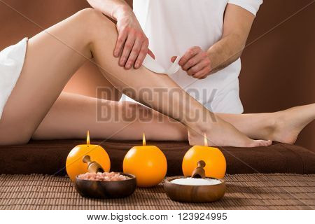Close-up Of A Woman Getting Her Leg Waxed By Applying Wax Strips At Beauty Spa