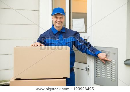Delivery Man Using Intercom To Enter Home For Delivery