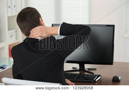 Businessman Suffering From Neck Pain While Working In Office