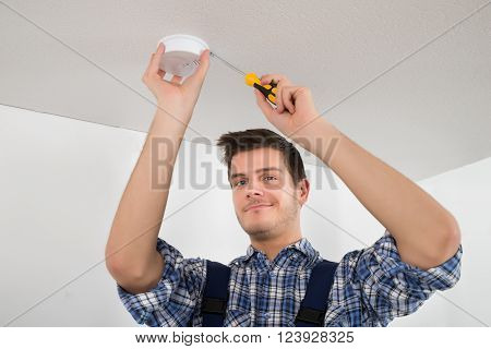 Male Electrician With Screwdriver Repairing Fire Sensor poster