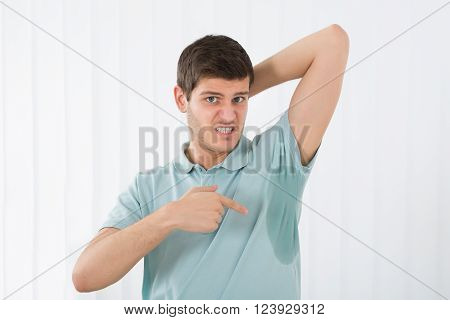 Young Man With Hyperhidrosis Pointing To A Sweat Armpit