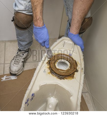 Plumber wearing kneepads installing a new toilet showing wax ring