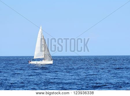 White sail yacht sailing in open Baltic sea on a clear sunny day