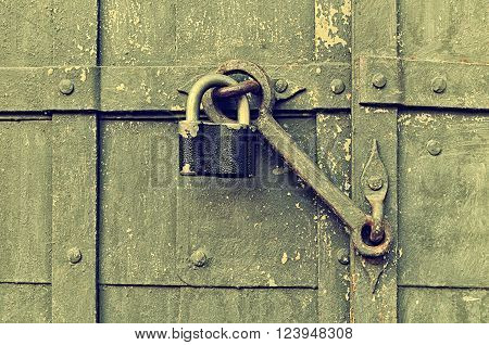 Metal black padlock with old door heck at the iron textured door. Selective focus at the padlock. Vintage filter applied ** Note: Visible grain at 100%, best at smaller sizes