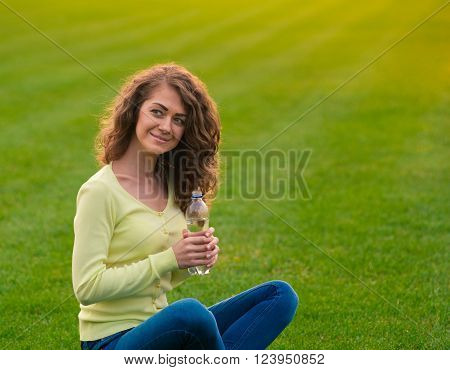 Young woman sitting with a bottle of water