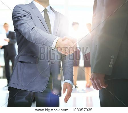 businessmen handshaking after striking deal. on a background sunrise