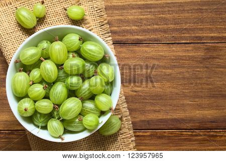 Raw gooseberries (lat. Ribes uva-crispa) in bowl, photographed overhead on dark wood with natural light (Selective Focus, Focus on the gooseberries on the top)