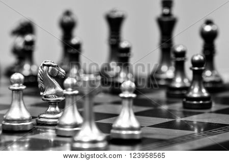 Chess board with white knight facing opponent in match