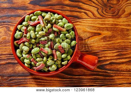 Tapas lima beans with iberico ham from Spain on wood