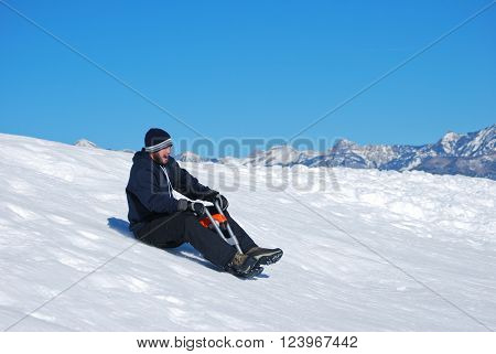 Man in toboggan on a motorcyle sled on a snowhill going down laughing.