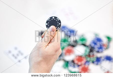 leisure, games, gambling and entertainment - close up of male hand holding casino chip and playing cards at home