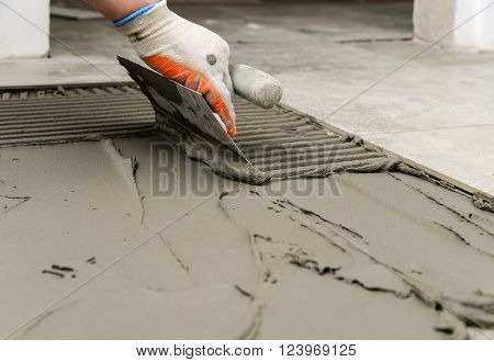 Laying Ceramic Tiles. Troweling mortar onto a concrete floor in preparation for laying floor tile.