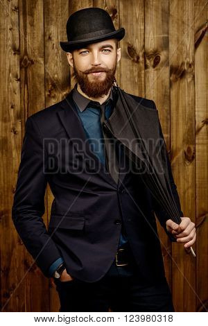 Elegant man with beard and mustache wearing suit and bowler hat. Old style fashion.
