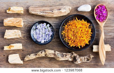 a set of stones sticks and colorful flower petals. aromatherapy herbal tea homeopathic medicine. zen like concepts