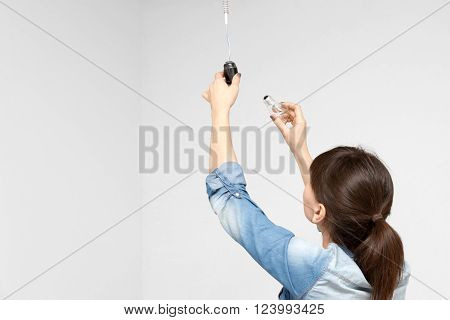 young woman changing light bulb on white