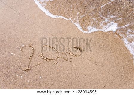 2016 inscription written in the wet beach sand being washed with sea water wave. Time passing away or New Year celebrating concept