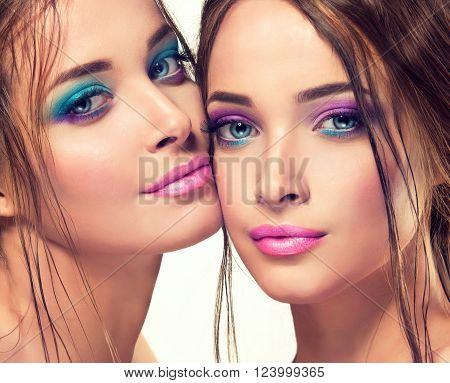 Beautiful young women with fashion make up . Girl twins with bright spring colored makeup . Fresh summer fashion image
